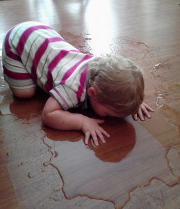 Baby drinking from puddle on floor. Plastic free baby. Reflective Mom.