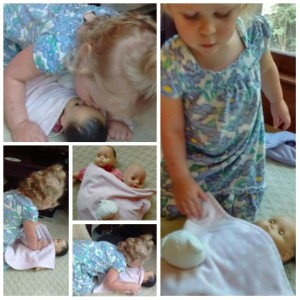 Toddler loving on baby dolls