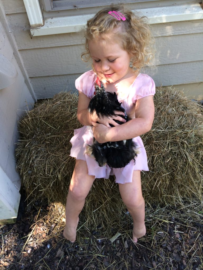 little girl in ballerina tutu with chicken